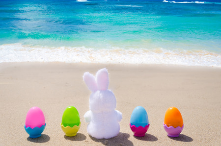Easter bunny and color eggs on the sandy beach by the ocean