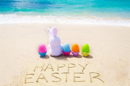 """Onderteken """"Gelukkige Pasen"""" met konijntje en kleureneieren op het zandige strand door de oceaan"""