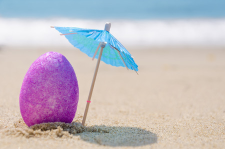 Purper paasei met cocktailparaplu op het zandige strand