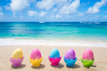Five easter eggs on the sandy beach photo
