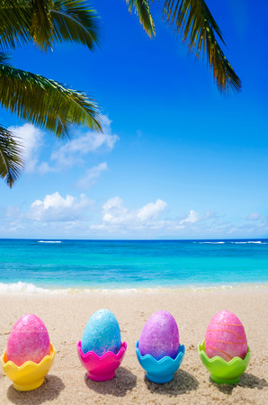 Four easter eggs on the sandy beach photo