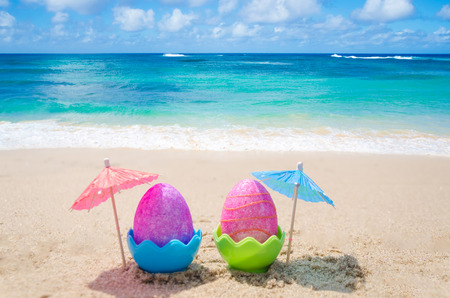 Two easter eggs with cocktail umbrella on the sandy beach photo