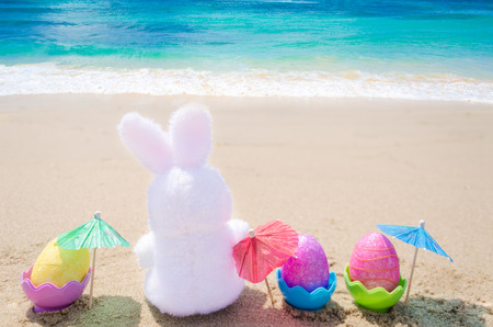 beach animals: Easter bunny and color eggs with cocktail umbrellas on the sandy beach by the ocean