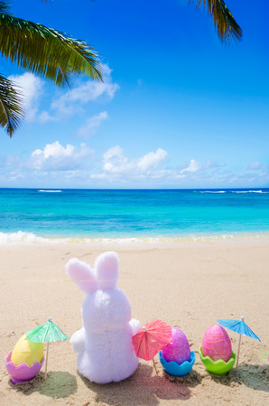 Easter bunny and color eggs with cocktail umbrellas on the sandy beach by the ocean photo