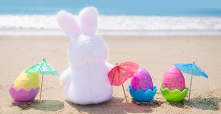 Easter bunny and color eggs with cocktail umbrellas on the sandy beach by the ocean
