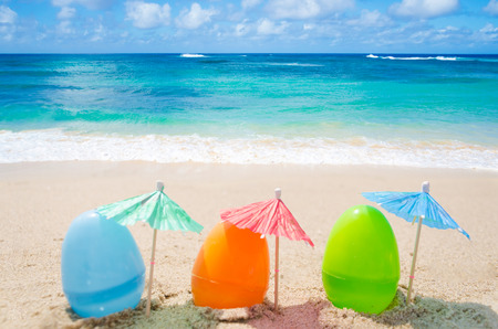 Three easter eggs with cocktail umbrella on the sandy beach