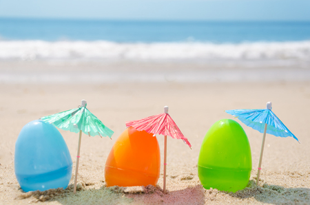 Three easter eggs with cocktail umbrella on the sandy beach photo