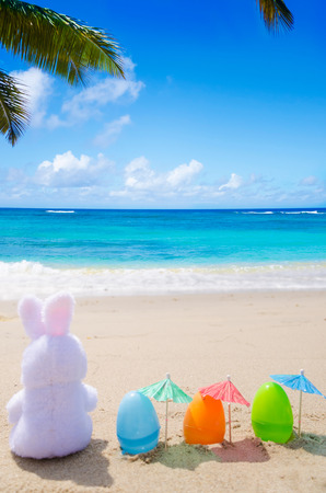 Easter bunny and color eggs with cocktail umbrella on the sandy beach by the ocean