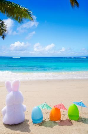 Paashaas en kleur eieren met cocktail paraplu op het strand aan de oceaan