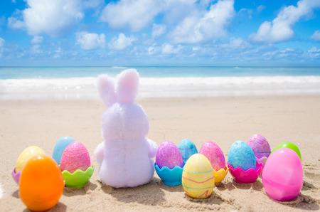 conejo: Conejo de Pascua y de colores los huevos en la playa de arena junto al mar