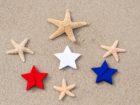 American holidays background with starfishes and color stars on the sand photo