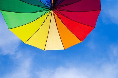 Rainbow umbrellas background against a blue sky photo