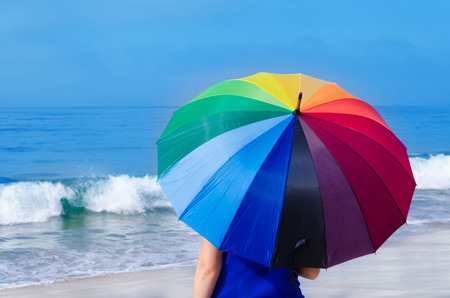 Girl with rainbow umbrella by the ocean photo