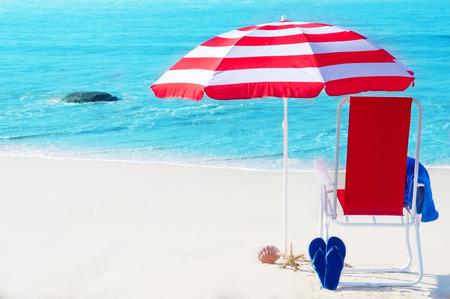Parasol de playa y silla por el océano en un día soleado Foto de archivo - 27568219