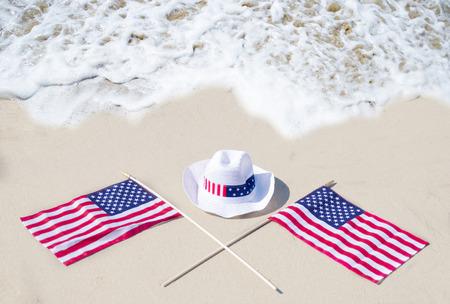union beach: American holidays hat and flags background on the sandy beach near the ocean