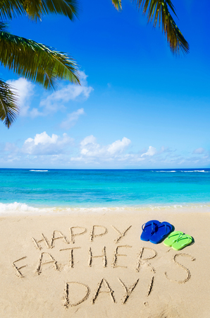 Happy fathers day background with flip flops on the sandy beach