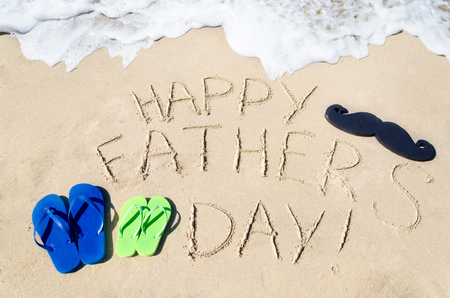 Happy fathers day background with flip flops on the sandy beach photo