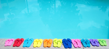 Color flip flops by the swimming pool in sunny day