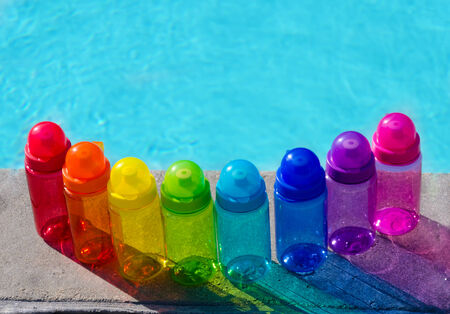 safe water: Color water bottles by the swimming pool in sunny day Stock Photo