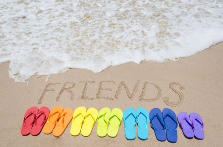Sign Friends and color flip flops on sandy beach by the ocean in sunny day photo