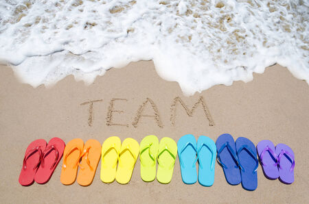 Sign Team and color flip flops on sandy beach by the ocean in sunny day
