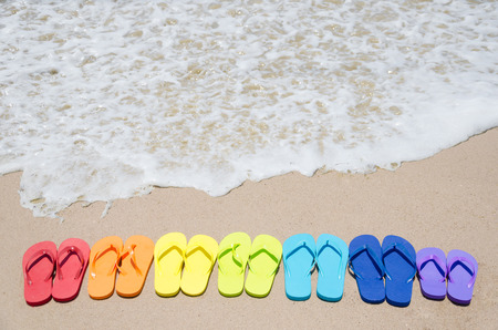 Color flip flops on sandy beach by the ocean on in sunny day photo