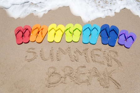 Sign Summer break and color flip flops on sandy beach by the ocean in sunny day photo