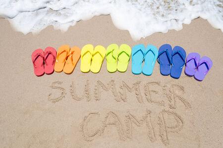 「夏キャンプ」を署名し、晴れた日の海で砂浜でフリップフ ロップを色 写真素材
