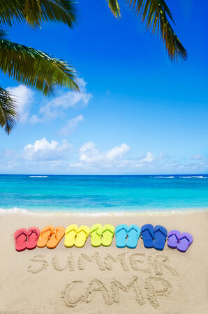 Sign Summer camp and color flip flops on sandy beach by the ocean in sunny day photo