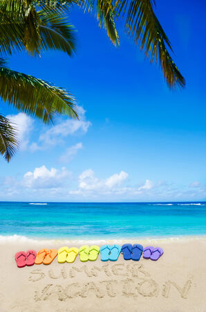 Sign Summer vacation and color flip flops on sandy beach by the ocean in sunny day photo