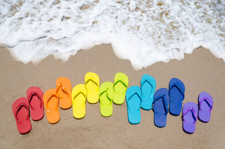 Color flip flops on sandy beach by the ocean in sunny day photo