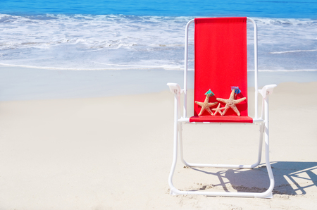 Beach chair with starfishes on the sandy beach by the ocean photo