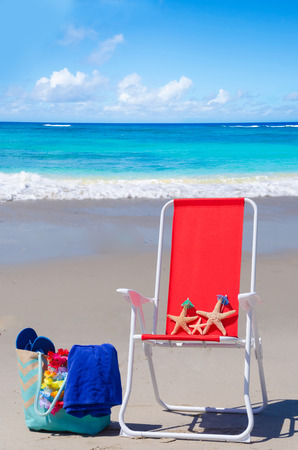 Beach chair with starfishes and bag on the sandy beach by the ocean photo