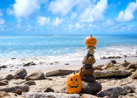 Two Halloween pumpkins on the beach by ocean photo