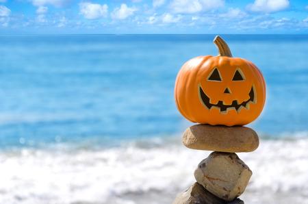 Halloween pompoen op het strand door de oceaan Stockfoto