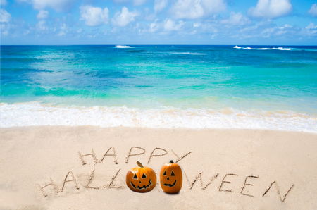 Sign Happy Halloween with pampkin on the sandy beach by ocean