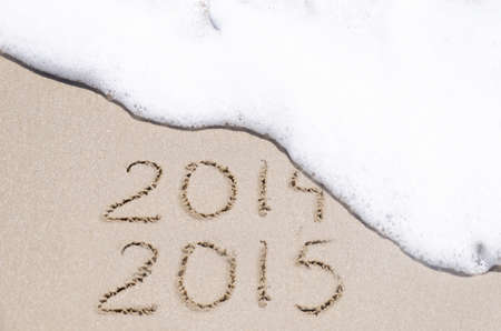 Sign 2014 and 2015 on the sandy beach by ocean photo