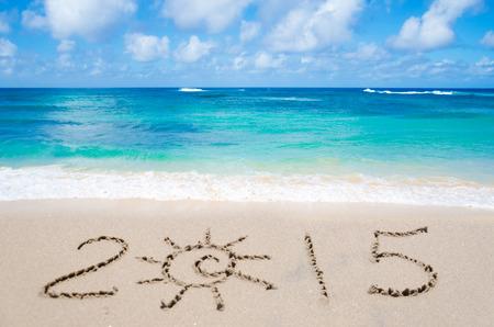 Sign 2015 on the sandy beach by ocean