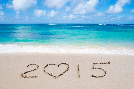 Sign 2015 with heart on the sandy beach by ocean photo