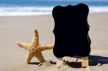 Black board with starfish on the sandy beach next to ocean photo