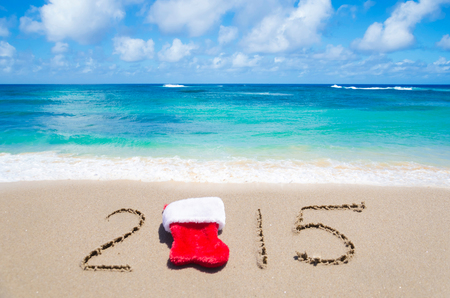 Sign 2015 with Christmas sock on the sandy beach by the ocean photo