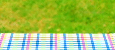 Picnic colorful tablecloth textile on the table with grass background Stock Photo