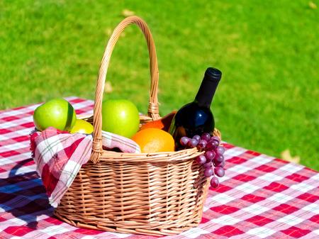 Picknick mand met fruit en wijn op gras achtergrond