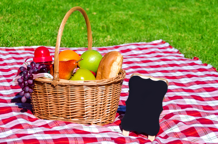 Picnic basket with fruits and blank on the grass background