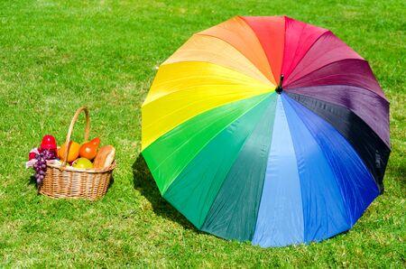 rainbow umbrella: Rainbow umbrella and Picnic basket with fruits on the grass background Stock Photo