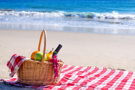 basket: Picnic background with basket and fruits by the ocean Stock Photo
