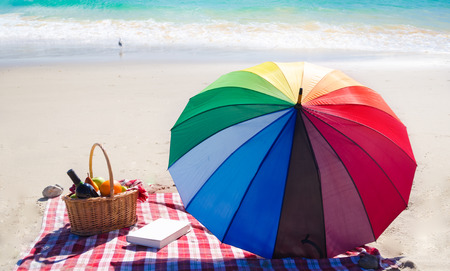 beach mat: Picnic background with basket, fruits, book and umbrella by the ocean