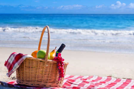 drink at the beach: Picnic background with basket and fruits by the ocean Stock Photo
