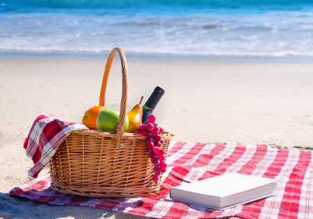 beach mat: Picnic background with basket, fruits and book by the ocean