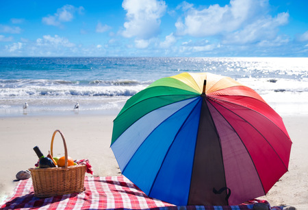 beach mat: Picnic background with basket, fruits and umbrella by the ocean